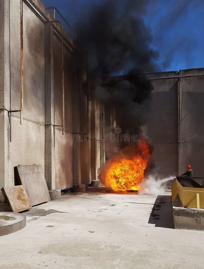 Der Feuerwehrmann löscht das Feuer mit Rauche aus lizenzfreie stockfotografie