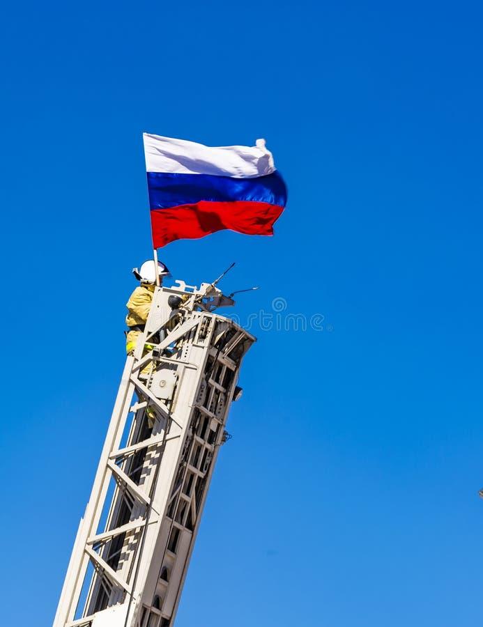 Der Feuerwehrmann sichert eine russische Flagge auf der Feuerleiter auf Hintergrund des blauen Himmels stockbild