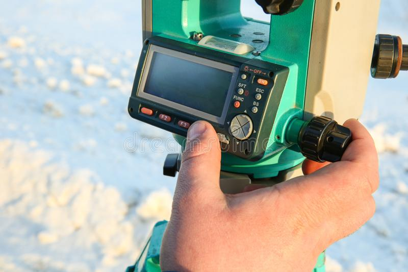 Der Finger des Feldmessers drückt den Knopf auf dem Tachymeter lizenzfreies stockfoto