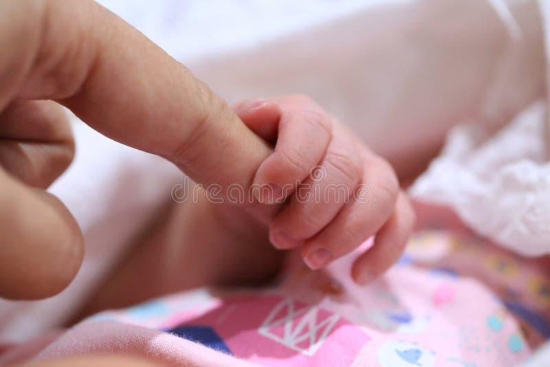 Der Finger der neugeborenen Babygriff-Mutter stockfoto