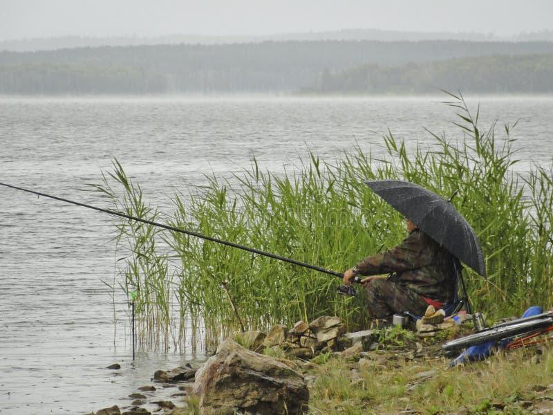 Der Fischer sitzt auf dem Ufer des Sees unter einem Regenschirm im regnerischen Wetter stockfotos