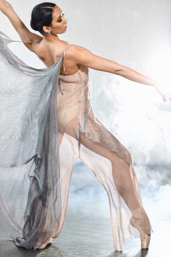 Der flexible Ballettt?nzer, der in die Dunkelheit ausdehnt, beleuchtete Studio stockfoto