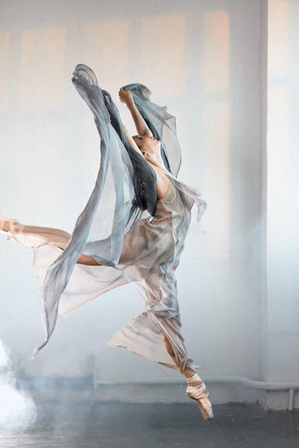 Der flexible Ballettt?nzer, der in die Dunkelheit ausdehnt, beleuchtete Studio lizenzfreie stockbilder