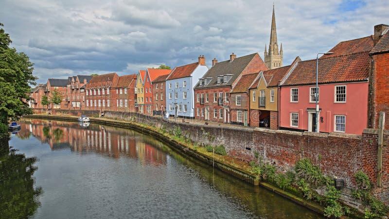 Der Flussuferfluß Wensum in Norwich Norfolk, Großbritannien mit bunten Häusern auf der linken Seite und die Fye-Brücke im Hinterg stockfotografie