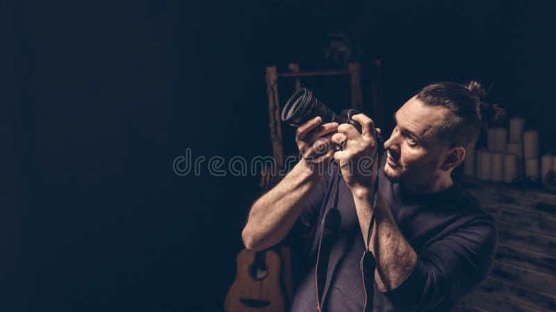 Der Fotograf hält die Kamera in seinen Händen, die das Aufpassen zielen stockfotos