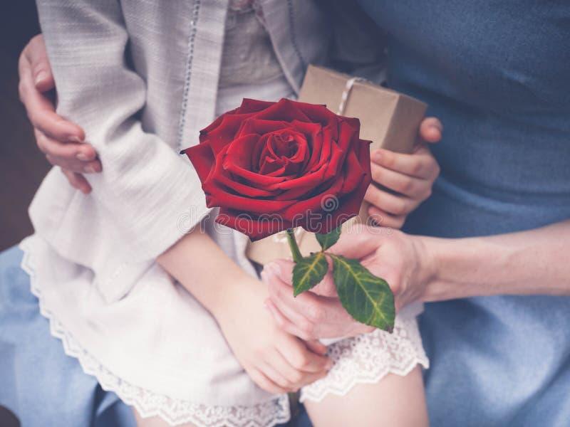 Der Frauen und die Hände der Kinder halten eine große Rose und ein Geschenk zusammen Glücklicher Mutter`s Tag lizenzfreies stockbild
