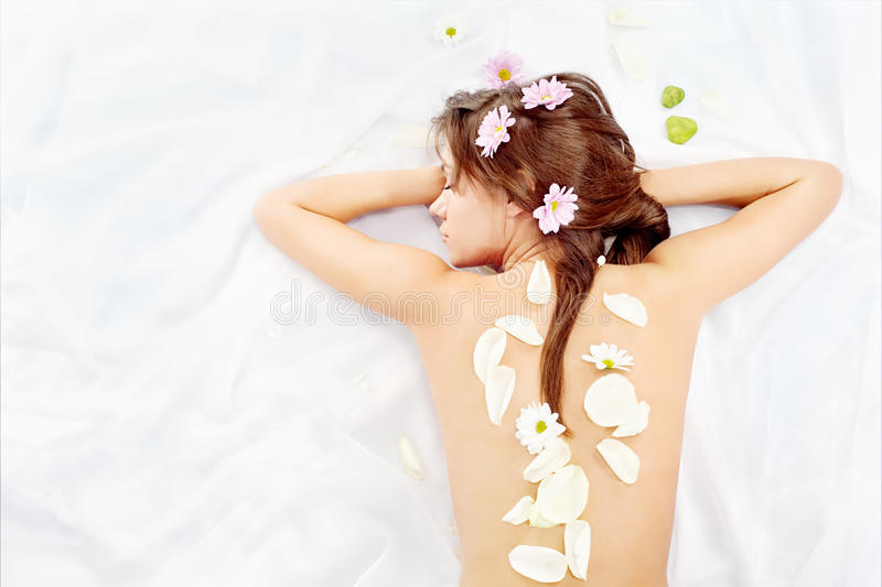 Der Frauen unterstützen bedeckt mit den Blumenblättern und den Blumen stockbilder