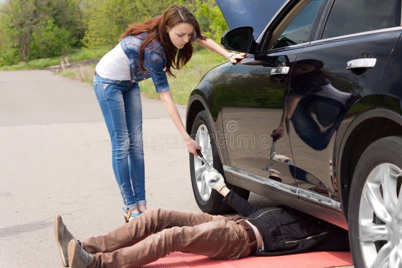 Der Frauenfahrer, der einen Mechaniker aufpasst, reparieren ihr Auto lizenzfreies stockfoto