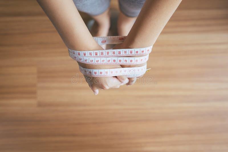Der Frauenfuß, der auf elektronischem steht, wiegen Skalen mit Maßband ihre gedrehten, Konzept Hände des Gewichtsverlusts, des Kö stockfoto