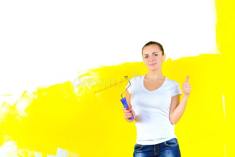Der Frauenmaler für das Malen der Wände, steht mit einer Rolle in der Hand lächelnd stockfotografie