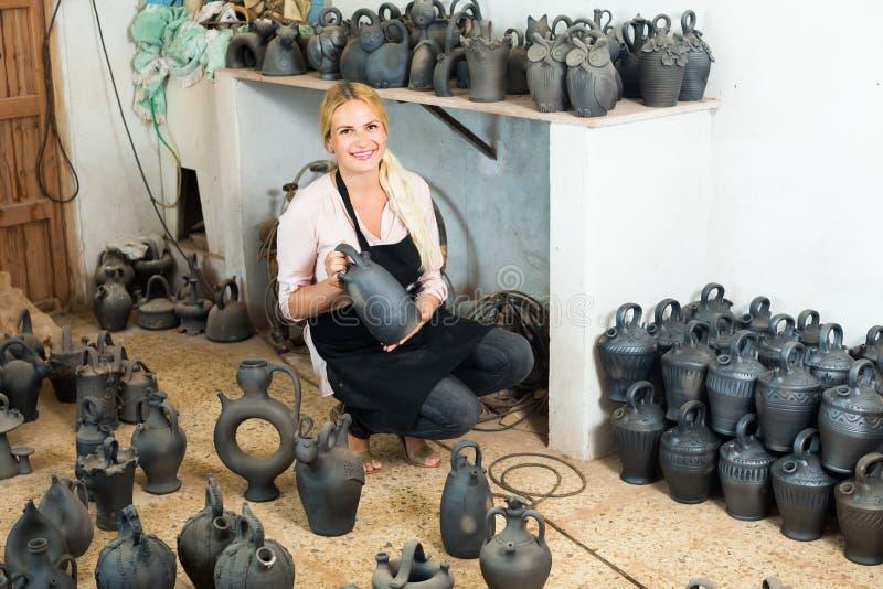 Der Frauentöpfer, der Schwarzes hält, glasierte Keramikschiffe im Studio lizenzfreies stockbild