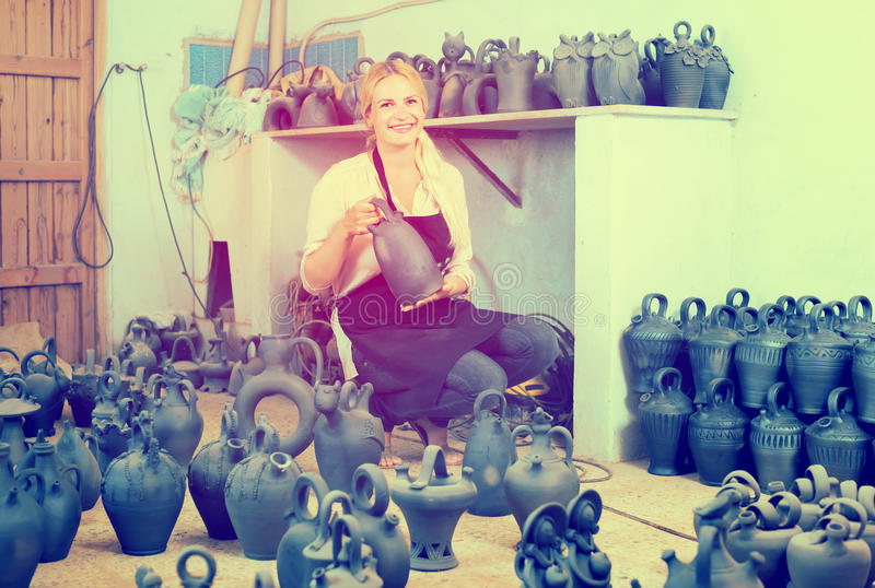 Der Frauentöpfer, der Schwarzes hält, glasierte Keramikschiffe im Studio lizenzfreie stockfotografie