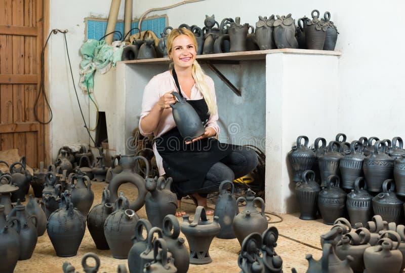 Der Frauentöpfer, der Schwarzes hält, glasierte Keramikschiffe im Studio stockfoto