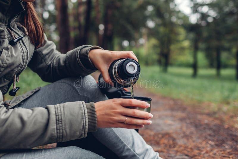 Der Frauentourist gießt heißen Tee aus Wald der Thermosflasche heraus im Frühjahr kampierend, Reisen und Sportkonzept stockfoto