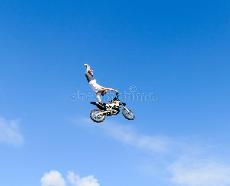 Der Freistil Viererkabel-Fahrradpilot macht einen Sprung mit einem Hochsprung mit einem Trick lizenzfreie stockbilder