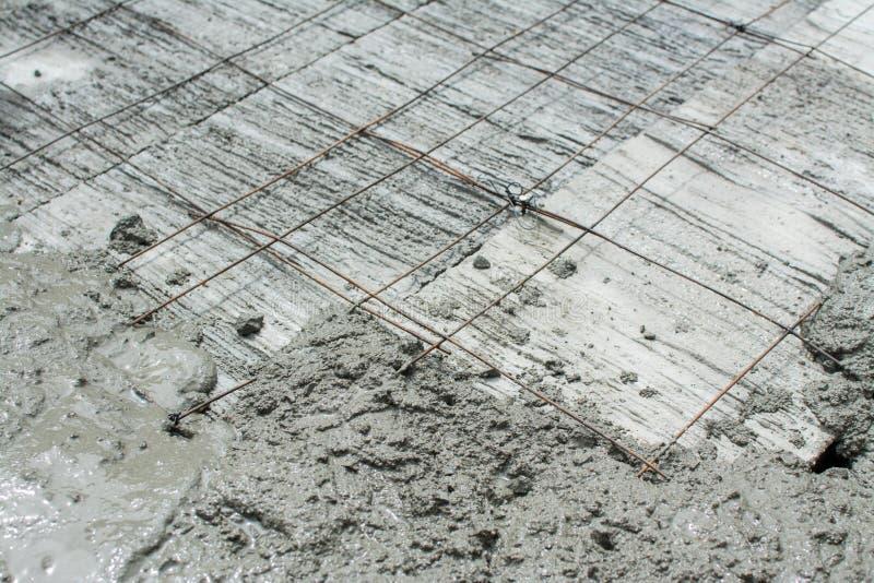 Der Frischbeton wird auf Maschendraht-Stahlverstärkung gegossen lizenzfreies stockbild