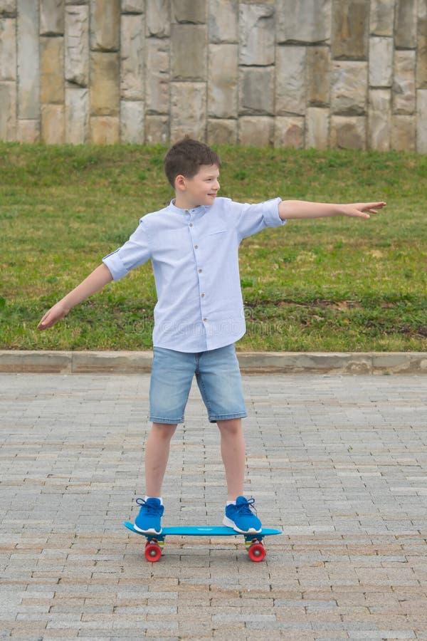 In der Frischluft fährt der Junge auf ein blaues Skateboard auf den Steinblöcken und bringt seine Hände vor lizenzfreie stockfotografie
