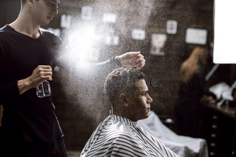 Der Friseur kleidete in schwarze Kleidung tut das Haar an, das zum stilvollen schwarz-haarigen Mann anredet, der im Lehnsessel si lizenzfreie stockfotografie