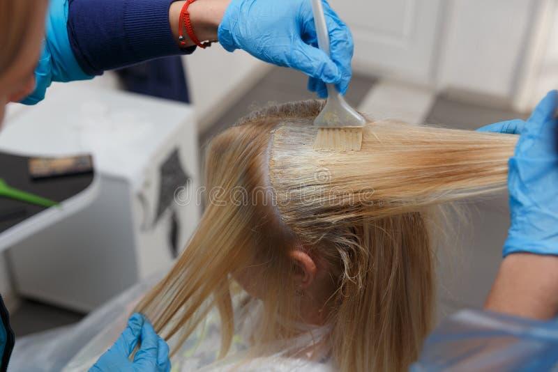 Der Friseur malt das Haar der Frau stockfotografie