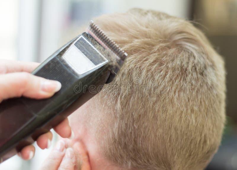 der Friseur schneidet den Jungentrimmer stockfotografie