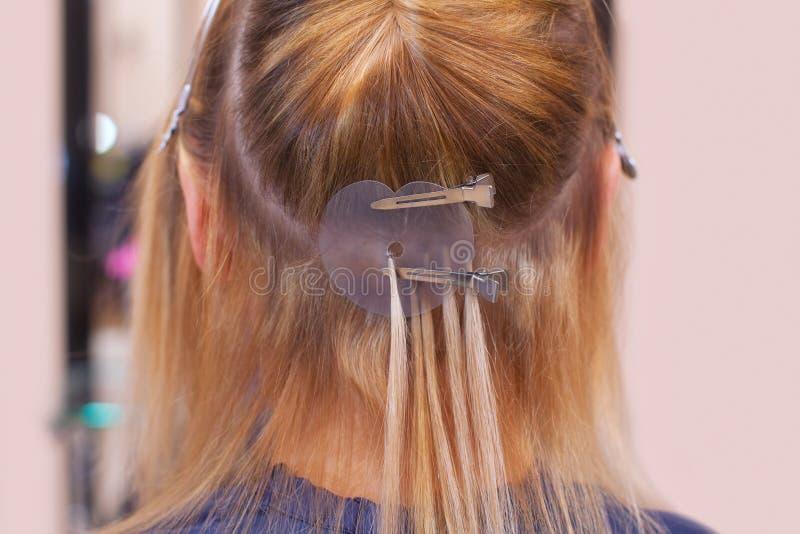 Der Friseur tut Haarerweiterungen ein junges Mädchen, eine Blondine in einem Schönheitssalon an stockfoto