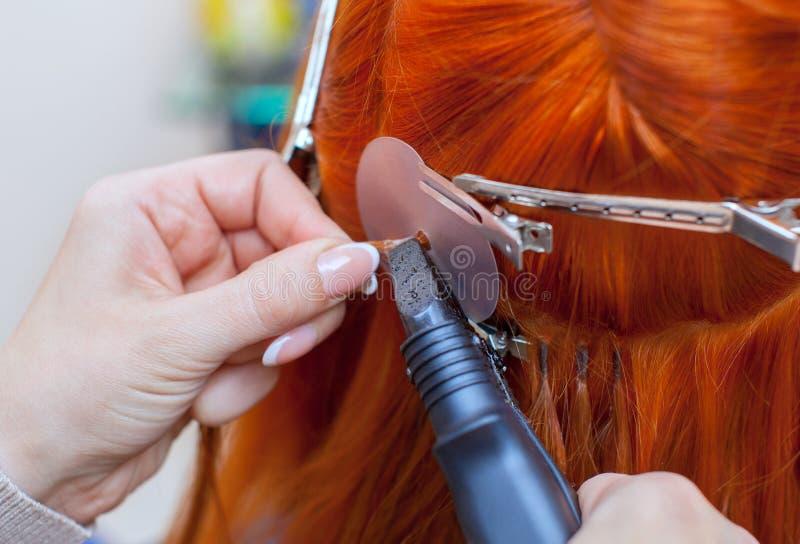 Der Friseur tut Haarerweiterungen ein junges, rothaariges Mädchen, in einem Schönheitssalon an stockfotografie