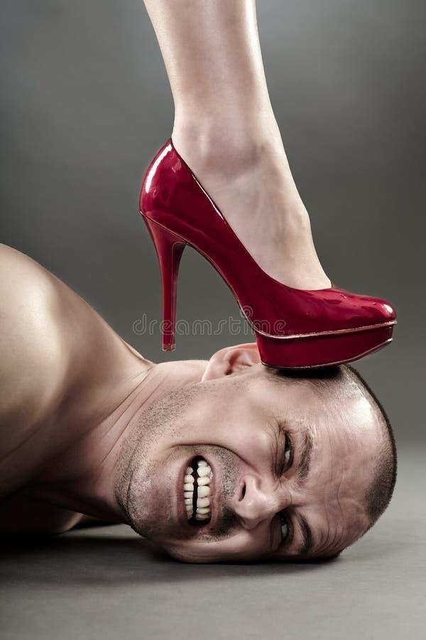 Der Fuß der Frau Männerkopf zerquetschend lizenzfreie stockfotos