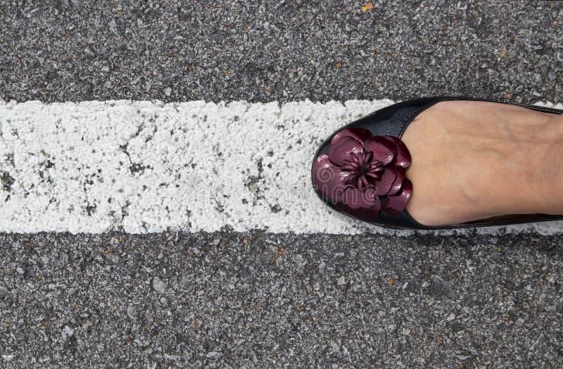 Der Fuß der Frau im Flachrückenschuh mit purpurroter Blume auf weißem Streifen auf Asphalt - gehend die Linie lizenzfreies stockfoto