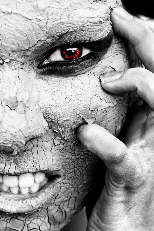 Der furchtsame Blick einer Frau mit trockener Haut und einem roten Auge stockbild
