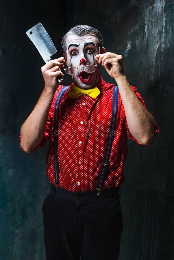 Der furchtsame Clown, der ein Messer auf dack hält Ein grimmiger Minireaper, der eine Sense anhält, steht auf einem Kalendertag,  stockbild