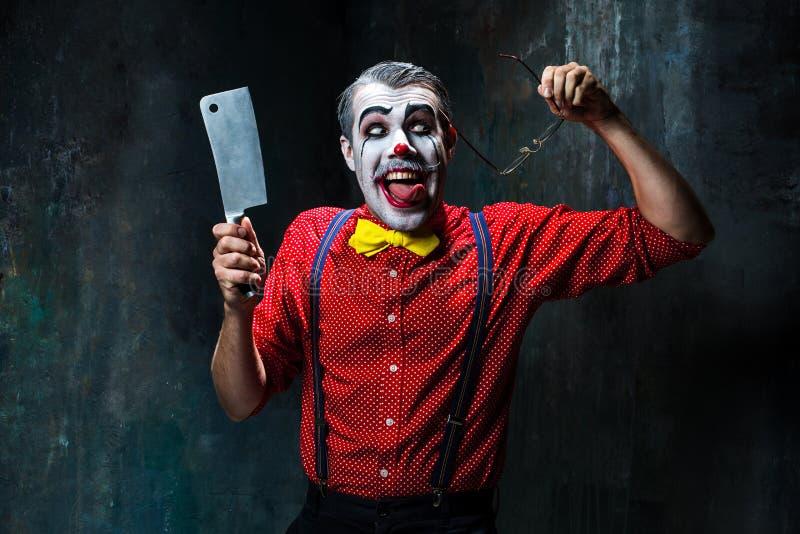 Der furchtsame Clown, der ein Messer auf dack hält Ein grimmiger Minireaper, der eine Sense anhält, steht auf einem Kalendertag,  lizenzfreies stockfoto