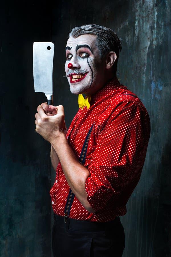 Der furchtsame Clown, der ein Messer auf dack hält Ein grimmiger Minireaper, der eine Sense anhält, steht auf einem Kalendertag,  lizenzfreie stockbilder