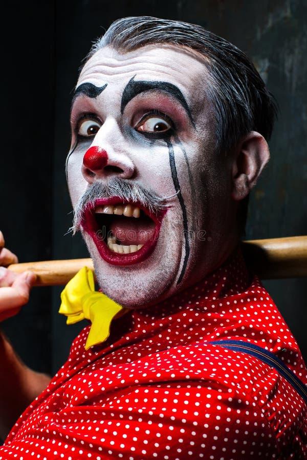 Der furchtsame Clown und der Baseballschläger auf dack Hintergrund Ein grimmiger Minireaper, der eine Sense anhält, steht auf ein stockfotografie