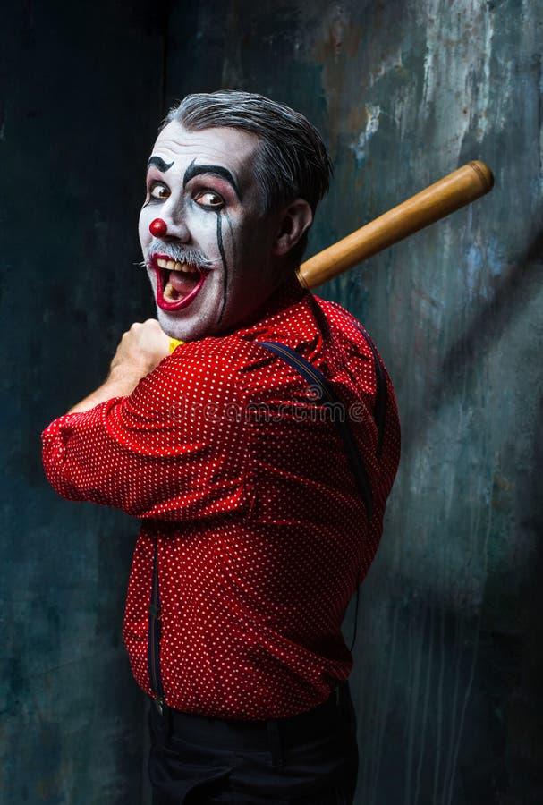 Der furchtsame Clown und der Baseballschläger auf dack Hintergrund Ein grimmiger Minireaper, der eine Sense anhält, steht auf ein lizenzfreies stockfoto