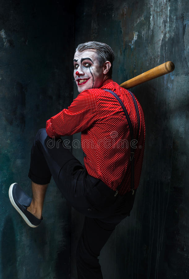 Der furchtsame Clown und der Baseballschläger auf dack Hintergrund Ein grimmiger Minireaper, der eine Sense anhält, steht auf ein stockbilder