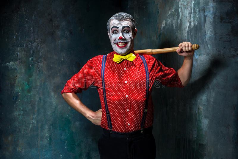 Der furchtsame Clown und der Baseballschläger auf dack Hintergrund Ein grimmiger Minireaper, der eine Sense anhält, steht auf ein lizenzfreie stockbilder