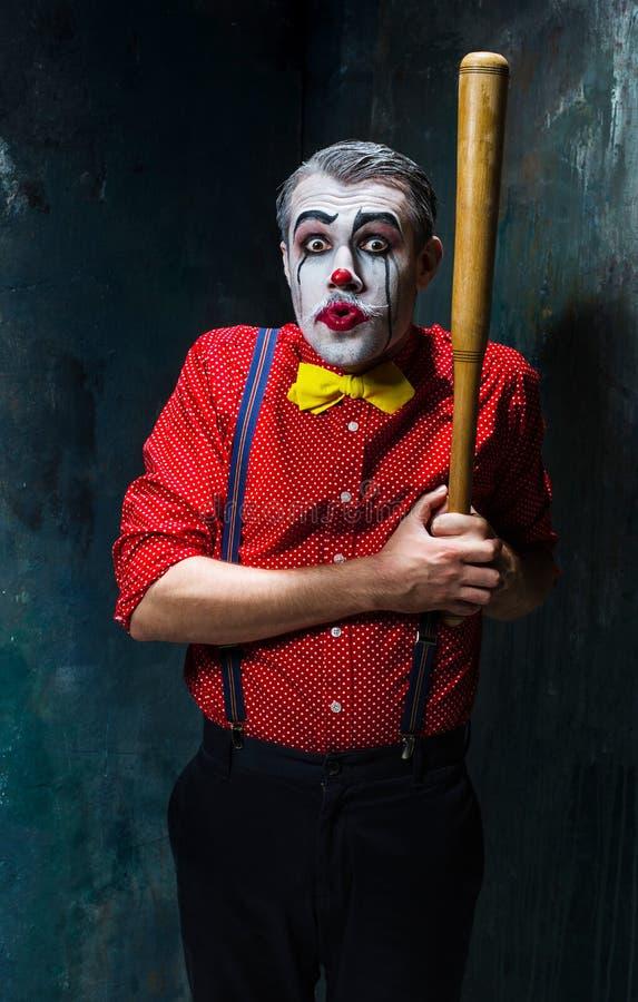 Der furchtsame Clown und der Baseballschläger auf dack Hintergrund Ein grimmiger Minireaper, der eine Sense anhält, steht auf ein lizenzfreie stockfotografie