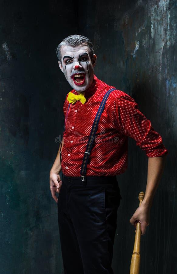 Der furchtsame Clown und der Baseballschläger auf dack Hintergrund Ein grimmiger Minireaper, der eine Sense anhält, steht auf ein lizenzfreies stockbild