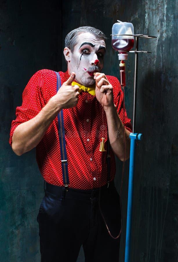 Der furchtsame Clown und der Tropfenfänger mit Blut auf dack Hintergrund Ein grimmiger Minireaper, der eine Sense anhält, steht a lizenzfreie stockfotos