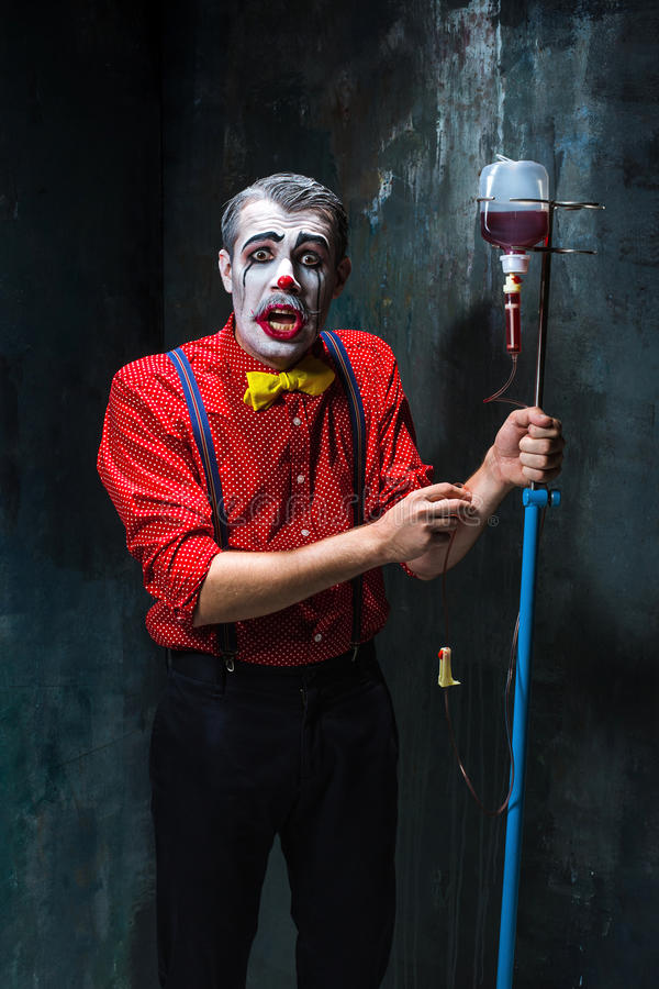 Der furchtsame Clown und der Tropfenfänger mit Blut auf dack Hintergrund Ein grimmiger Minireaper, der eine Sense anhält, steht a stockfotografie