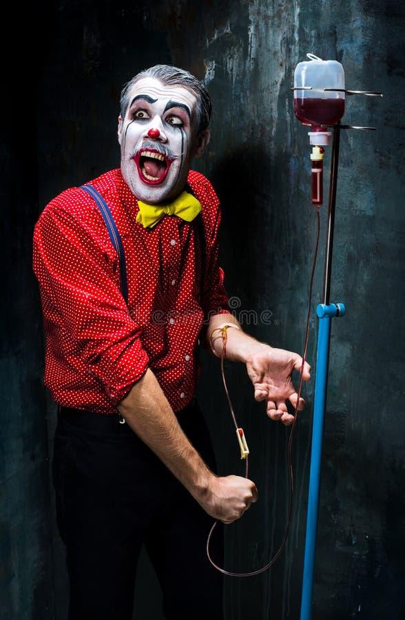 Der furchtsame Clown und der Tropfenfänger mit Blut auf dack Hintergrund Ein grimmiger Minireaper, der eine Sense anhält, steht a stockfoto