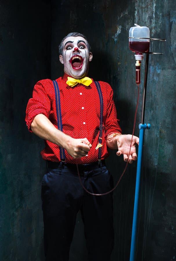 Der furchtsame Clown und der Tropfenfänger mit Blut auf dack Hintergrund Ein grimmiger Minireaper, der eine Sense anhält, steht a lizenzfreie stockbilder