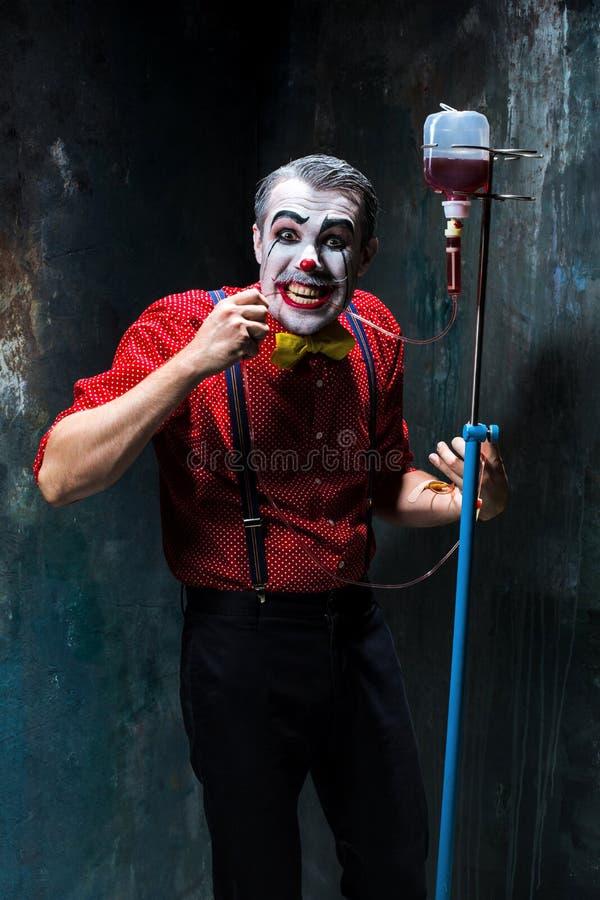Der furchtsame Clown und der Tropfenfänger mit Blut auf dack Hintergrund Ein grimmiger Minireaper, der eine Sense anhält, steht a lizenzfreie stockfotografie