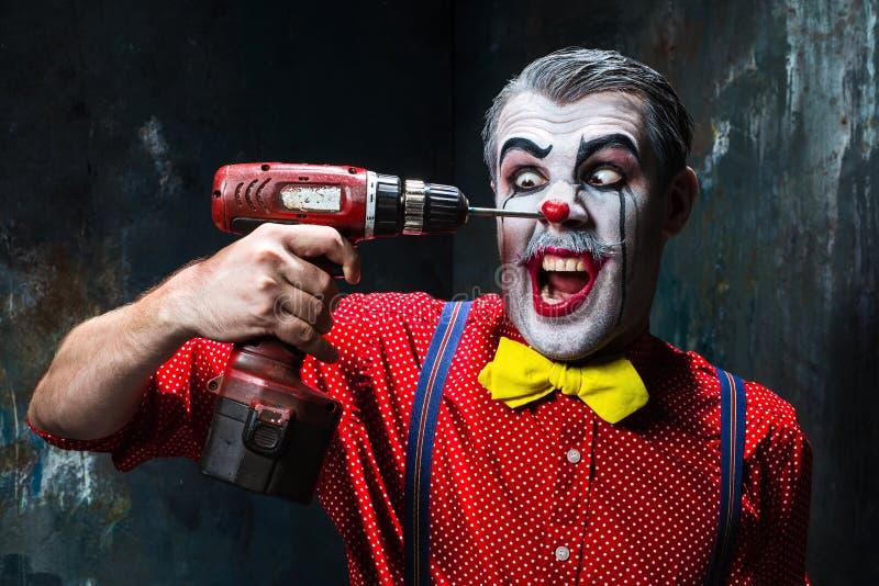 Der furchtsame Clown und die elektrische Bohrmaschine auf dack Hintergrund Ein grimmiger Minireaper, der eine Sense anhält, steht lizenzfreies stockbild