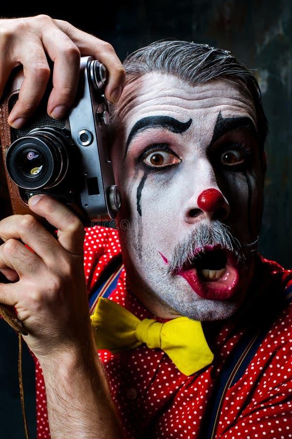 Der furchtsame Clown und eine Kamera auf dack Hintergrund Ein grimmiger Minireaper, der eine Sense anhält, steht auf einem Kalend stockbild