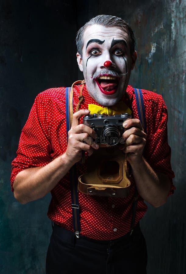 Der furchtsame Clown und eine Kamera auf dack Hintergrund Ein grimmiger Minireaper, der eine Sense anhält, steht auf einem Kalend lizenzfreie stockfotografie