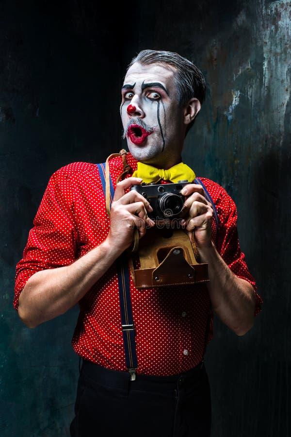 Der furchtsame Clown und eine Kamera auf dack Hintergrund Ein grimmiger Minireaper, der eine Sense anhält, steht auf einem Kalend lizenzfreie stockbilder