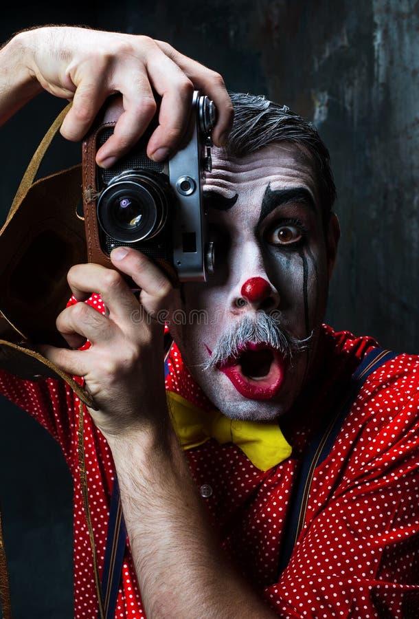 Der furchtsame Clown und eine Kamera auf dack Hintergrund Ein grimmiger Minireaper, der eine Sense anhält, steht auf einem Kalend lizenzfreie stockfotos