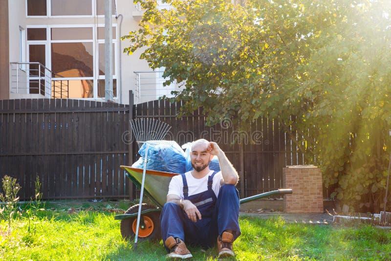 Der Gärtner sitzt auf dem Gras, das auf einem Wagen mit Werkzeugen sich lehnt Die Strahlen der Sonne von der rechten Seite stockbild