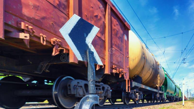 Der Güterzug hetzt hinter dem Pfeil stockfotografie